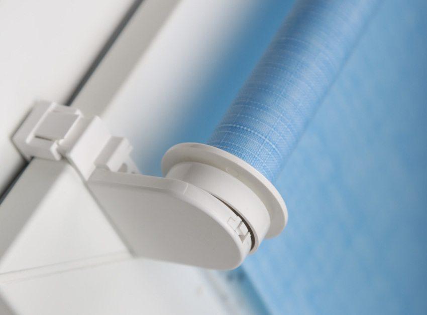 Рулонная штора наматывается на пластиковый вал, который крепится к оконной раме