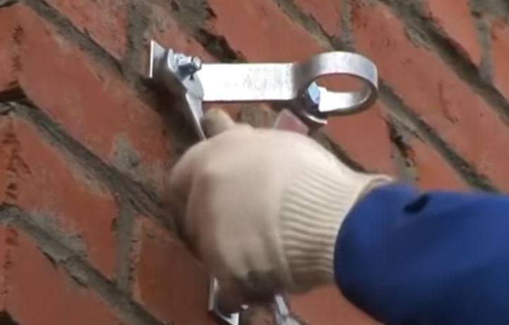 монтаж кронштейна СИП на фасаде дома
