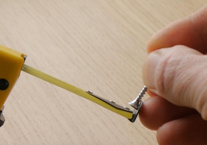 использование отверстия в рулетке для зацепа шурупа